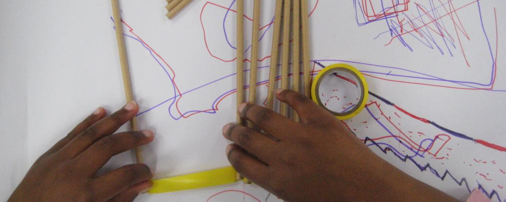 A child's hands sticking paper straws to a red and purple scribbled drawing