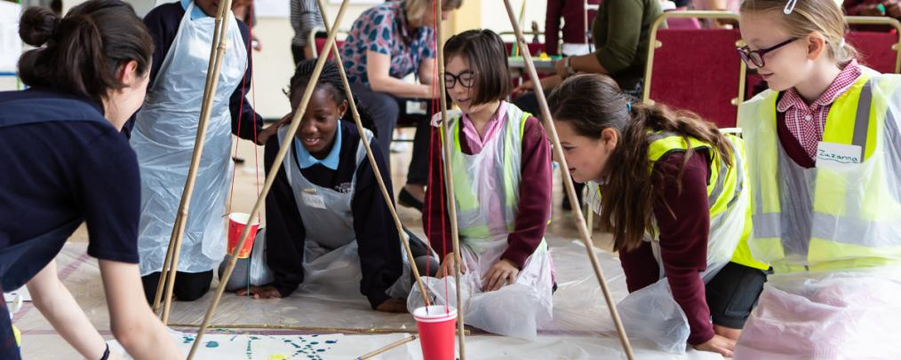 Children sitting on the floor creating a blue splatter painting and bamboo structure