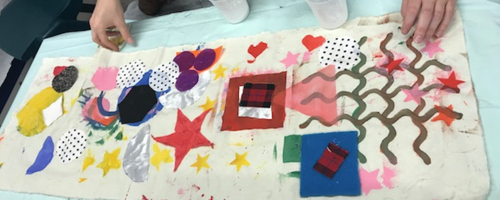 Two children make a colourful fabric collage using repeated geometric shapes and pattern