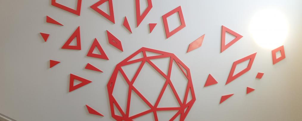 A mural in a school stairwell showing coral coloured geometric shapes