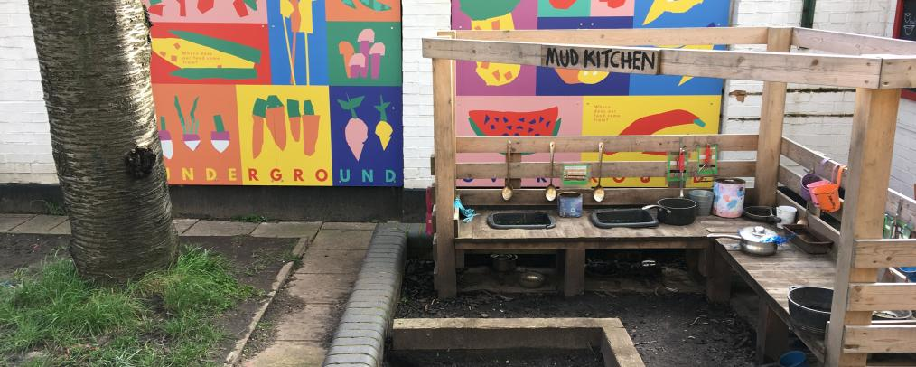 Mud Kitchen in a school playground with two colourful murals behind depicting fruit and vegetables