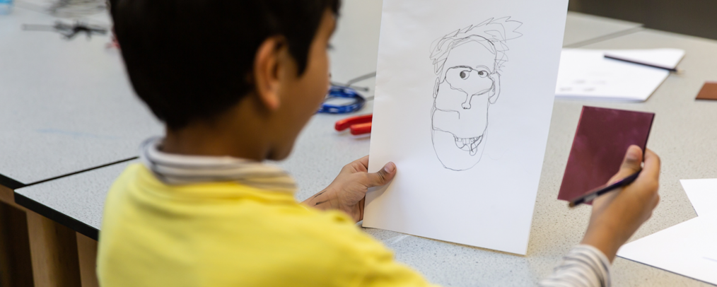 A child with a mirror in one hand and a continuous line self-portrait in the other