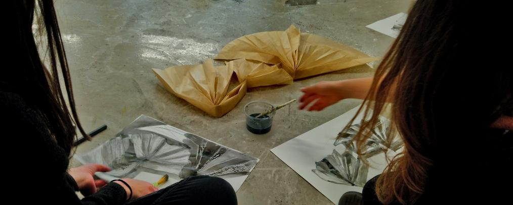 Two teachers making pen and ink drawings of a paper sculpture