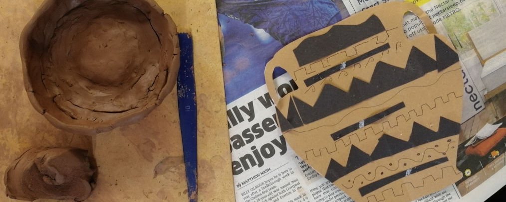 A cardboard collage of a Greek pot next to a half-made clay pot