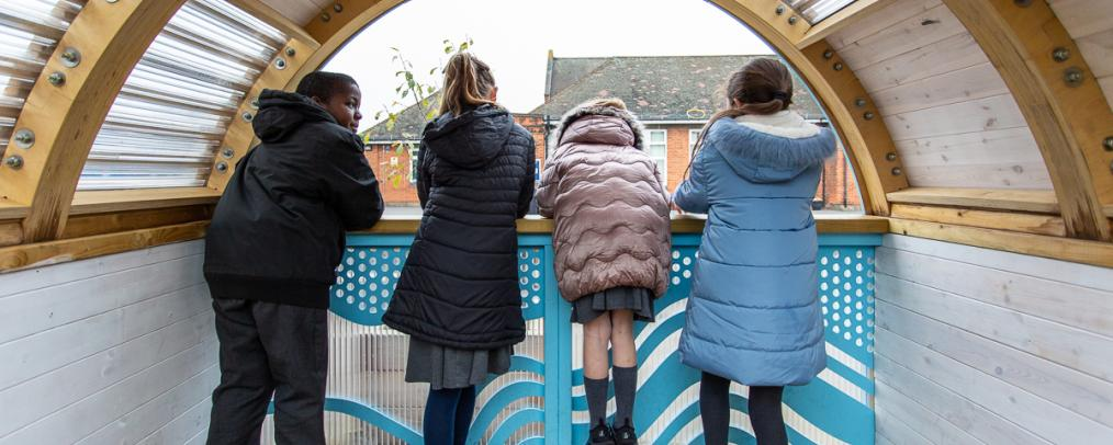 Four children looking out of an enclosed structure onto the school playground